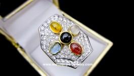 แหวนเพชรพลอย ทรง Fortunate Ring ใช้เพชร 97-98 VVS น้ำหนักเพชรรวม 2.43 ct ตัวเรือนทองคำ 90 น้ำหนักรวม 18 กรัม ประกอบด้วย ทับทิม, นิล, มุกดาหาร, บุษราคัม และเพทาย